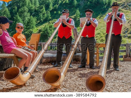 Him August mountain hut, by Ovronnaz village, Valais, Martigny-August 23, 2009: A band of three Swiss horn players entertain the guests at the lodge during a cheese and potatoes party, Switzerland - stock photo
