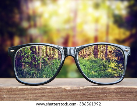 hipster glasses on a park bench or table with a forest in the background toned with a retro vintage instagram filter app or action effect  - stock photo