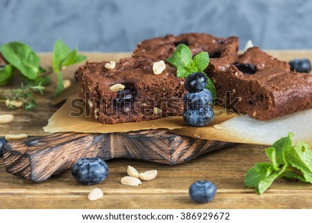 ?hocolate brownie with peanuts, blueberries,mint on a wooden table - stock photo