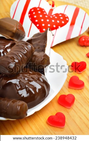 ��¡hocolate candies and a valentine heart on white plate on wooden background. - stock photo