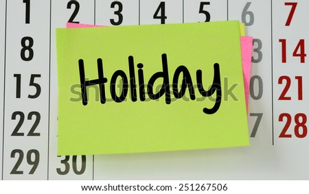 Holiday on calendar background. The phrase holiday on sticky paper note stuck to a wall calendar background - stock photo