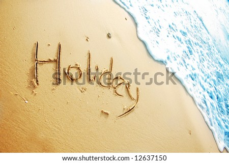 """Holiday"" written in the sand on the beach blue waves in the background - stock photo"