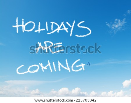 """holidays are coming"" written in the sky with contrails left by airplane - stock photo"