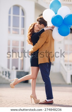 holidays, celebration and dating concept - couple with colorful balloons in the city. Happy couple with colorful balloons outdoors.  - stock photo
