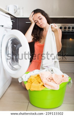 Home laundry. Unhappy  girl doing housework at home - stock photo