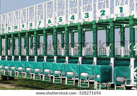 Horse track with starting gates at a race track summertime - stock photo