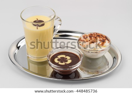 hot white chocolate in a glass with a little hot dark chocolate and cream in glass bowls served on a platter on white backround - stock photo