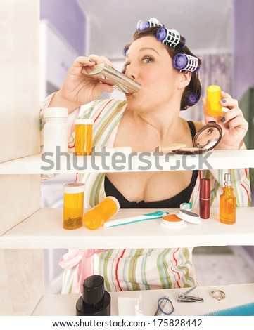 housewife taking pills and drinking in the bathroom  - stock photo
