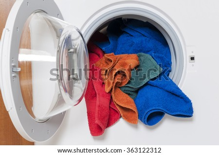 Housework, laundry service, washing machine with colored laundry. - stock photo