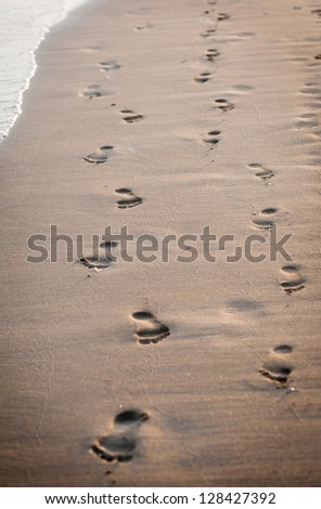 human footprints on the beach sand.Traces on the beach of a man and a woman.Footsteps on the beach by the sea in summer - stock photo