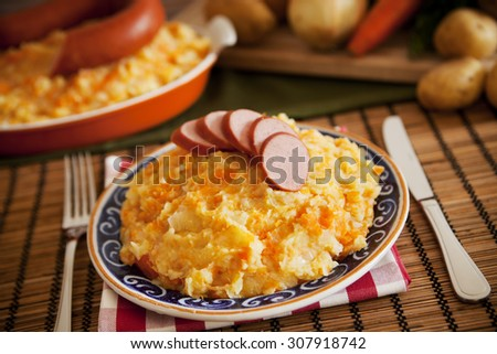 'Hutspot met worst' - a traditional Dutch dish with mashed potatoes, carrots, onions and smoked sausage. - stock photo