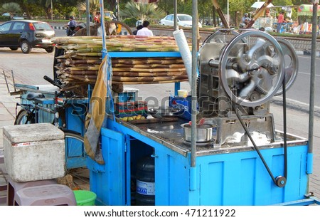 HYDERABAD,INDIA-AUGUST 19: street vendor use machine to crush sugar cane to make juice on a cart on busy road on August 19,2016 in Hyderabad,India