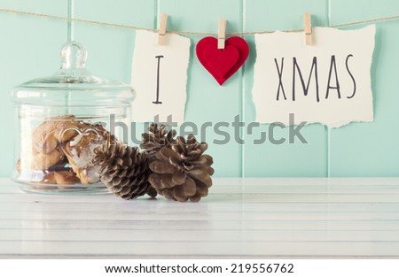 """I love xmas"" hanging on a rope with clothespins. A robin egg blue wainscot as background and a glass jar and pinecones on a white wooden table. Vintage Style. - stock photo"