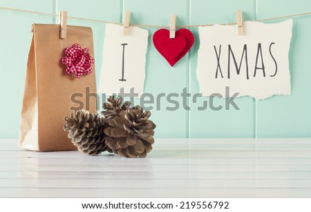 """I love xmas"" hanging on a rope with clothespins. A robin egg blue wainscot as background and a gift and some pinecones on a white wooden table. Vintage Style. - stock photo"