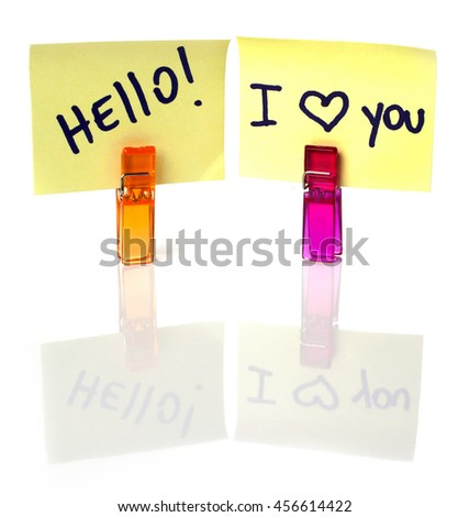 """I love you and hello"" message written on a yellow paper note with a clothespins holding isolated over a white background - stock photo"