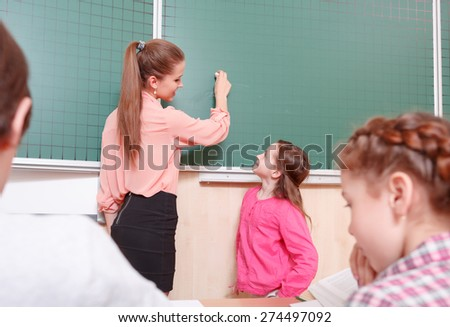 I will write. Smiling female teacher and pupil standing at blackboard, teacher is going to write on blackboard.