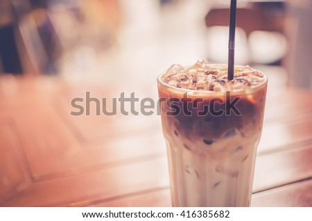 Ice coffee on wood table background. Shallow dept of field. Drink background concept. Retro color style. - stock photo