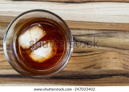 2 ice cubes floating in a glass with Kentucky straight Bourbon, served on a wooden table - stock photo