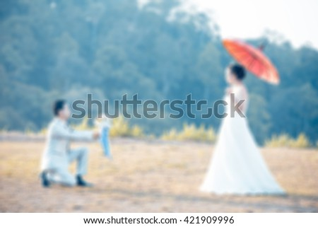 Image blur soft vintage ,groom kneel in front of the bride wed. And in that hand flowers - stock photo
