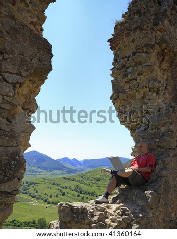 Image of a man working on a laptop outdoors.