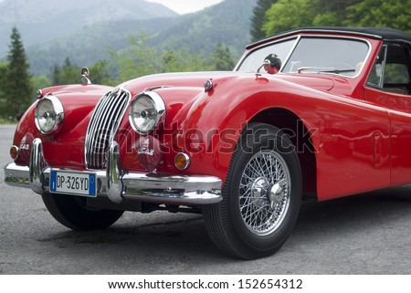 IMPERIA, ITALY - MAY 14: Red colored Jaguar cruising on the road in Imperia, Italy on May 14, 2011. - stock photo