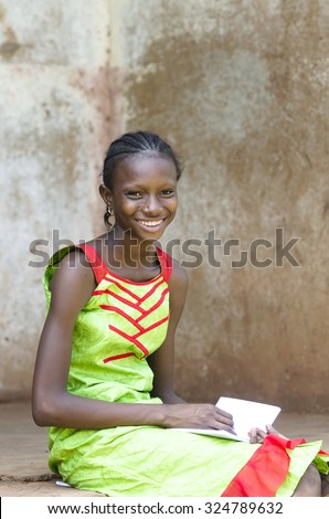 In Bamako (Mali), a young schoolgirl is concentrated while drawing on her exercise book. Smiling African black Girl in a school environment outside her classroom. - stock photo