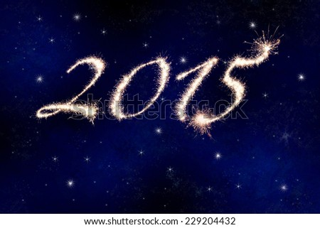 2015 in fireworks or sparklers against the night sky with stars celebrating the New Year. - stock photo