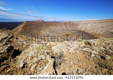 in los volcanes volcanic timanfaya  rock stone sky  hill and summer  lanzarote spain plant flower bush - stock photo
