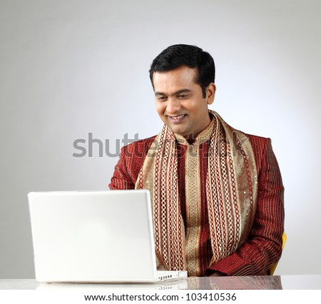 indian man in traditional clothing using laptop