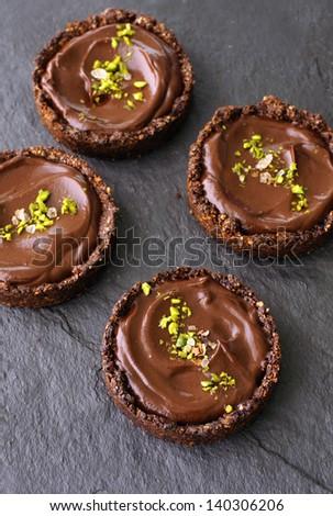 4 individual chocolate avocado pudding whole grain tarts on a black slate stone surface, sprinkled with pistachio and sea salt - stock photo