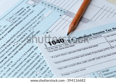 1040 Individual Income Tax Return Form for 2015 year with a pencil to fill on the white desk, close up