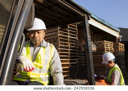 Industrial engineer smiling on forklift with partner on background