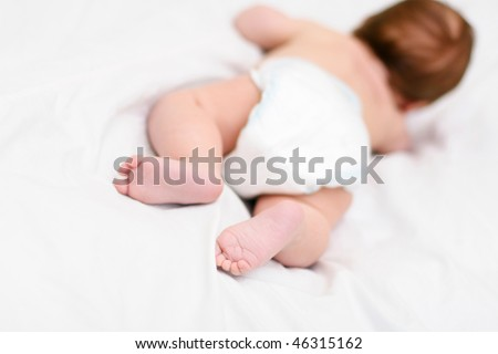 infant lying on the bed - stock photo