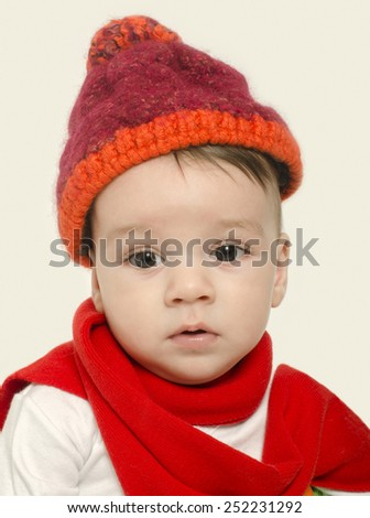 Innocent baby wearing a red hat and a muffler and looking adorable. Small kid dressed for winter, lovely newborn - stock photo