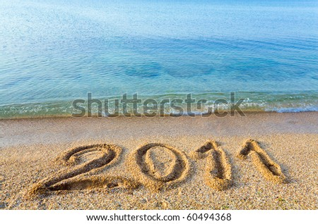 2011 inscription on sandy beach and morning sheen sea water surface