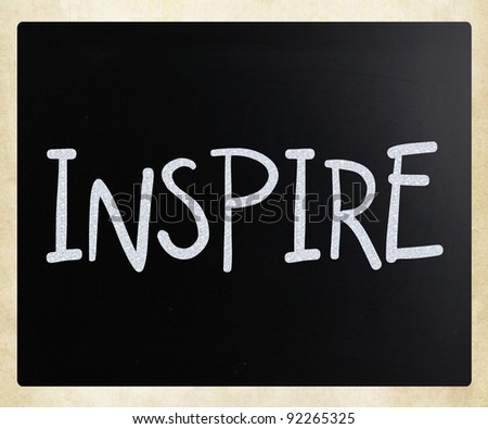 """Inspire"" handwritten with white chalk on a blackboard - stock photo"