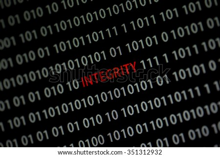 'Integrity' word in the middle of the computer screen surrounded by numbers zero and one. Image is taken in a small angle.