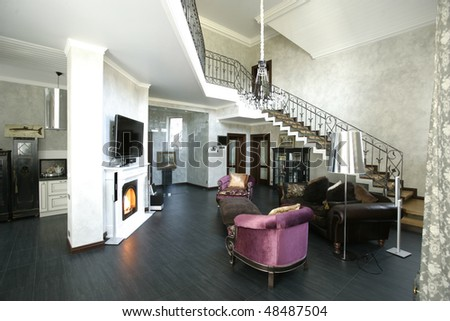 interior of a living room with fireplace and stair - stock photo