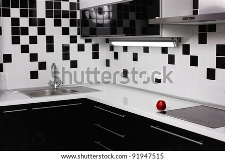 interior of black and white modern kitchen with red tasty apple - stock photo