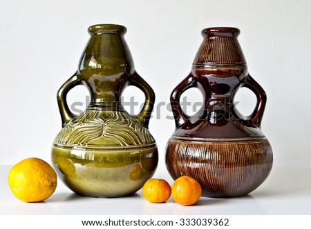 Israeli ceramic pair in  brown tones with orange fruits. Two vases of 1950-th years  Abstract carved, glazed images,.Symbolizes couple: He and She; brother and sister etc. Isolated on white. - stock photo
