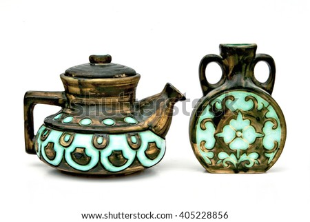 Israeli ceramic pair in dark brown tones: teapot and jug of 1950-th years with glazed inserts of aquamarine color.Symbolizes couple: He - She, brother - sister, bride - groom  etc. Isolated on white. - stock photo