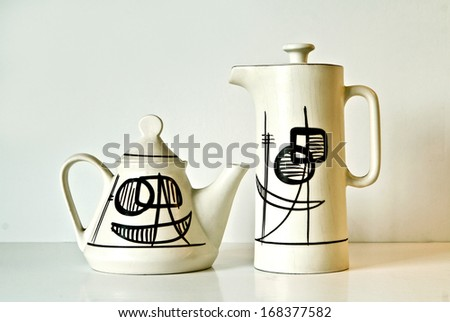 Israeli ceramic pair in light brown tones: two teapots of 1950-th  with abstract geometrical images.Symbolizes couple: He and She, brother and sister, bride and groom  etc. Isolated on white. - stock photo