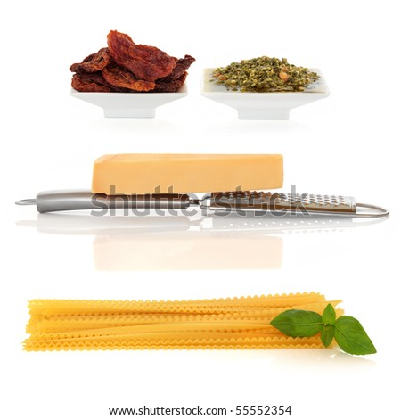 Italian food ingredients of pasta with basil herb,  parmesan cheese and grater, sun dried tomatoes and pesto sauce,  isolated over white background. - stock photo