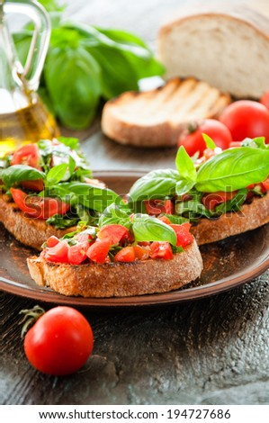 Italian tomato bruschetta with chopped vegetables, herbs and oil on grilled or toasted crusty ciabatta bread - stock photo