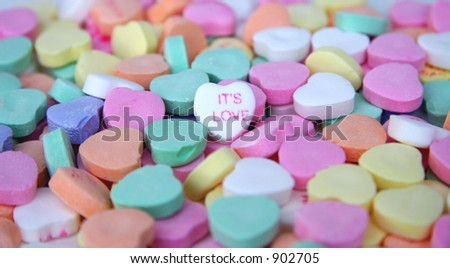 """""""Its Love"""" candy heart surrounded by other candy hearts. - stock photo"""