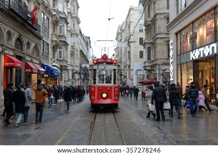 02 January 2016, Istanbul - Turkey: The Taksim Tunel Nostalgia Tram trundles along the istiklal street and people at istiklal avenue - stock photo