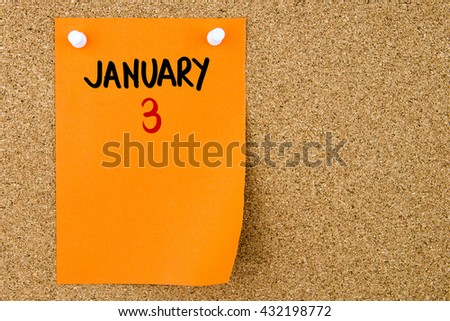 3 JANUARY written on orange paper note pinned on cork board with white thumbtacks, copy space available - stock photo