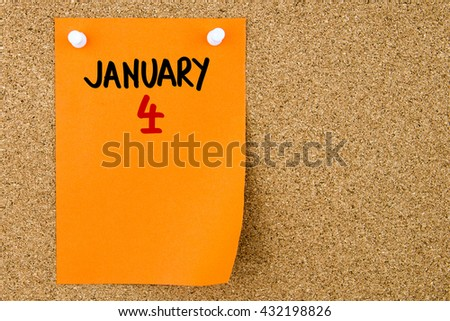 4 JANUARY written on orange paper note pinned on cork board with white thumbtacks, copy space available - stock photo