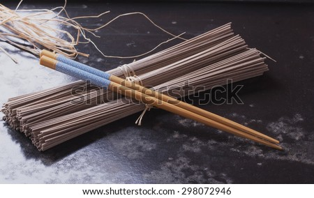 Japanese Soba noodles on a vintage wooden background with the chop sticks