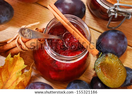 jar of homemade plum jam with cinnamon and fresh fruits on wooden table - top view - stock photo